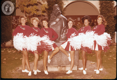 Cheerleaders pose with Montezuma sculpture